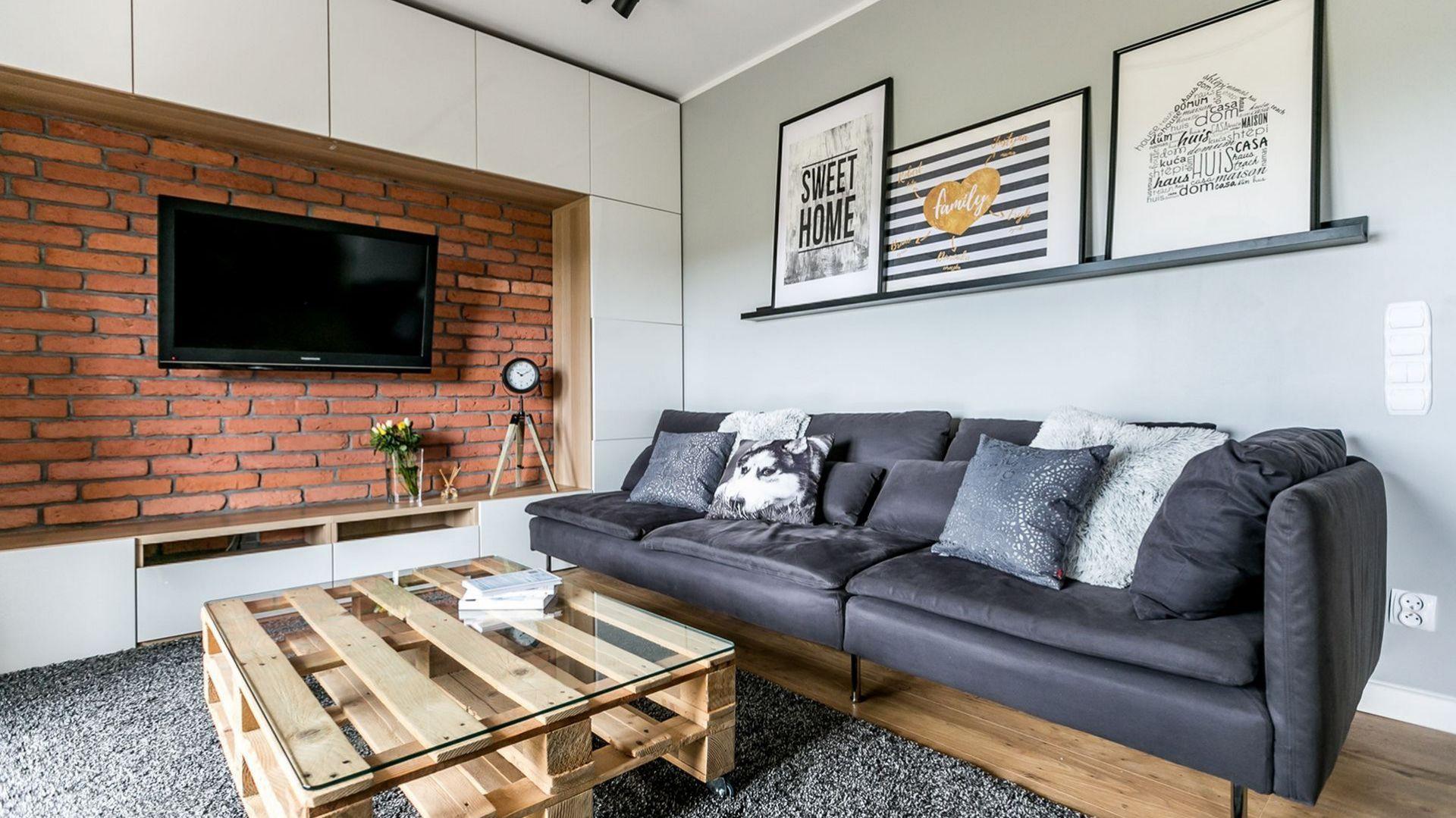 Ściana za telewizorem piękne prezentuje się w otoczeniu bieli, szarości i drewna.  Projekt: Urszula Chojnowska. Fot. Elżbieta Toczyłowska (Kreacje Domowe)