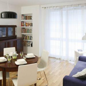 Stylizowany kreden oraz stół w połączeniu z niebieską sofą tworzą eklektyczny klimat małego salonu. Projekt: Ewelina Para. Fot. Bartosz Jarosz