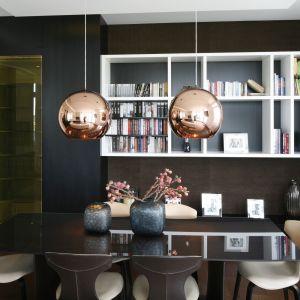 Regał za stołem w połączonej z salonem jadalni stanowi praktyczną ozdobę wnętrza. Projekt Agnieszka Hajdas-Obajtek