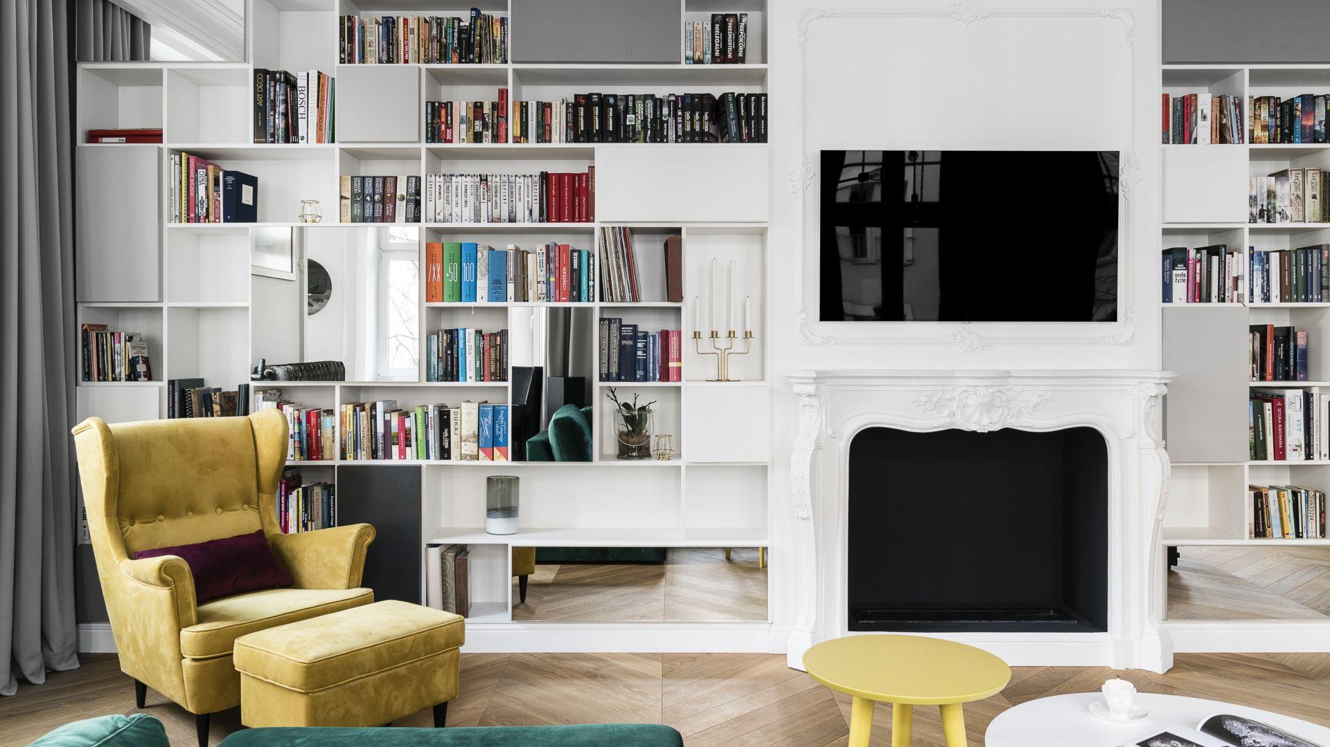 Regały na ścianie z kominkiem budują klimat domowej biblioteki. Projekt Anna Maria Sokołowska. Fot. Fotomohito