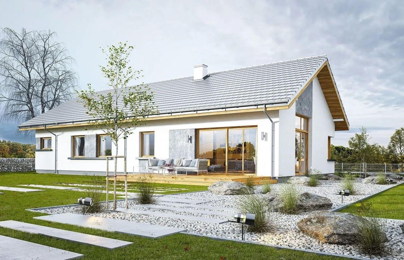 W szczycie i z tyłu domu salon zdobią duże przeszklenia otwierające wnętrze na otaczający ogród. Projekt: arch. Michał Gąsiorowski. Fot. MG Projekt