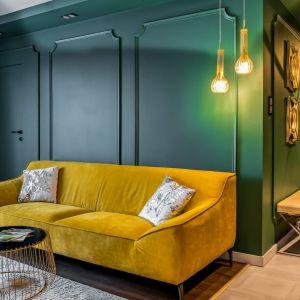 Na tyle ściany w kolorze butelkowej zielenie pięknie prezentuje się żółta kanapa. Projekt: Donata Gadalska. Fot. Jacek Fabiszewski