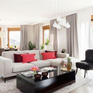 Czerwone poduszki stanowią doskonały kontrast na tle jasnej aranżacji salonu. Projekt: Katarzyna Maciejewska. Fot. Anna Laskowska