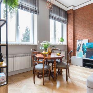 Dopełnieniem stylistyki vintage we wnętrzu jest ściana z czerwonej cegły. Na jej tle świetnie kontrastują elementy z czarnej stali, z kolei pozostające w przewadze szarości (mebli i pozostałych ścian) stanowią spokojne tło, które pięknie ją eksponują.Projekt: Monika Pniewska. Fot. Marta Behling / Pion Poziom