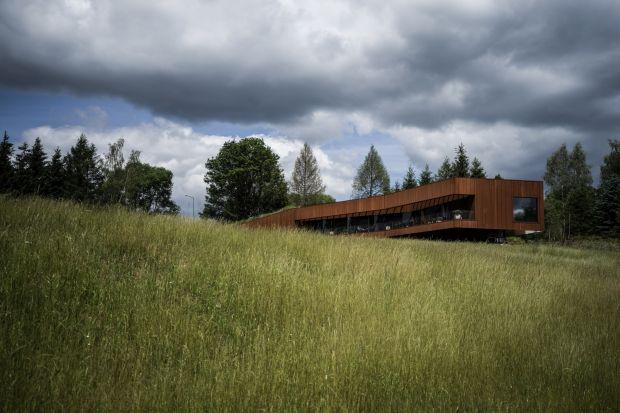 Architektura domu lokalizuje go na granicy z przyrodą. Od drogi pozostanie nieogrodzony. Drzewa, które udało się zachować uzupełniono nowymi nasadzeniami. Strukturę ziemną z darnią naciągnęliśmy na dach, aby jeszcze mocniej wpisać dom w konte