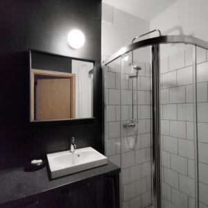 Niewielką łazienkę podzielono na strefę czarną, w której znalazła się toaleta i umywalka oraz białą – z kabiną prysznicową. Projekt: Agnieszka Musiał. Fot. Musiał Studio