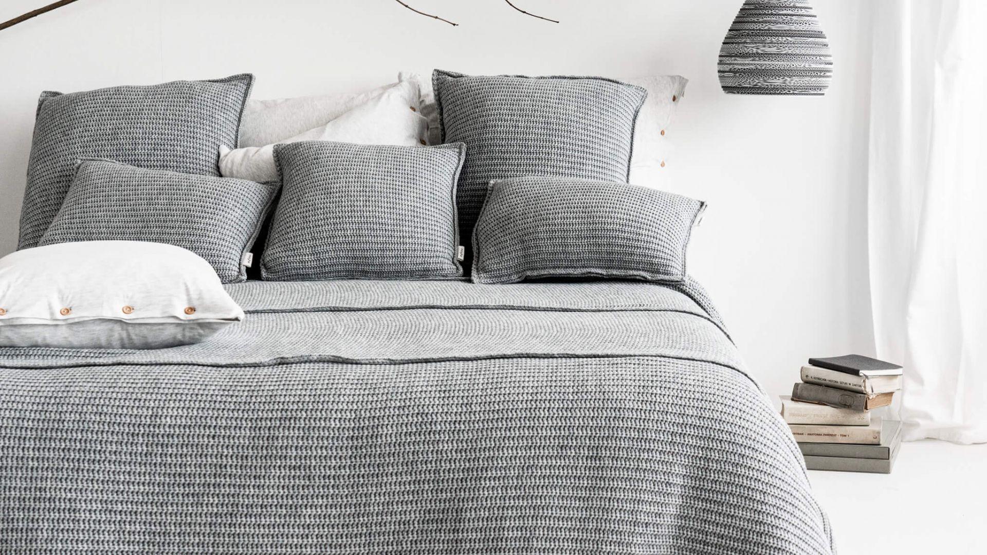 Wełniana szara narzuta z prostym wzorem w parze z równie uroczymi poduszkami. Narzuta - 699 zł, poduszka - 159 zł. Marka: Moyha