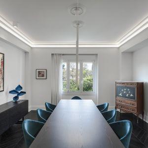 """W pokojach dominuje tradycyjny kolor biały, widoczny wszędzie na ścianach i sufitach, w tym na gipsowych listwach sufitowych """"ton w ton"""" podkreślonych liniowym oświetleniem i na delikatnych listwach podłogowych stykających się z podłogą w kolorze wengè. Studio projektowe: AK Praxis GP. Zdjęcia: Mariana Bisti"""