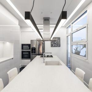 Kuchnia w kolorze total white - z wyjątkiem obrazów i podłogi - to wąskie i długie pomieszczenie, na środku którego znajduje się szeroka wyspa centralna ze strefą gotowania, zlewem oraz zintegrowanym barkiem. Studio projektowe: AK Praxis GP. Zdjęcia: Mariana Bisti