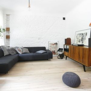 Kontrastem dla jasnych ścian i podłogi jest szara, ciemna kanapa oraz drewniana szafka. Projekt: Ewelina Pik. Fot. Bartosz Jarosz