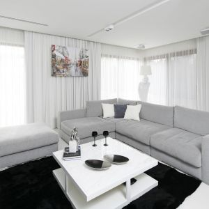Salon urządzono w bielach i szarościach, które ożywiają dodatki w czarnych kolorach. Projekt: Małgorzata Muc, Joanna Scott. Fot. Bartosz Jarosz