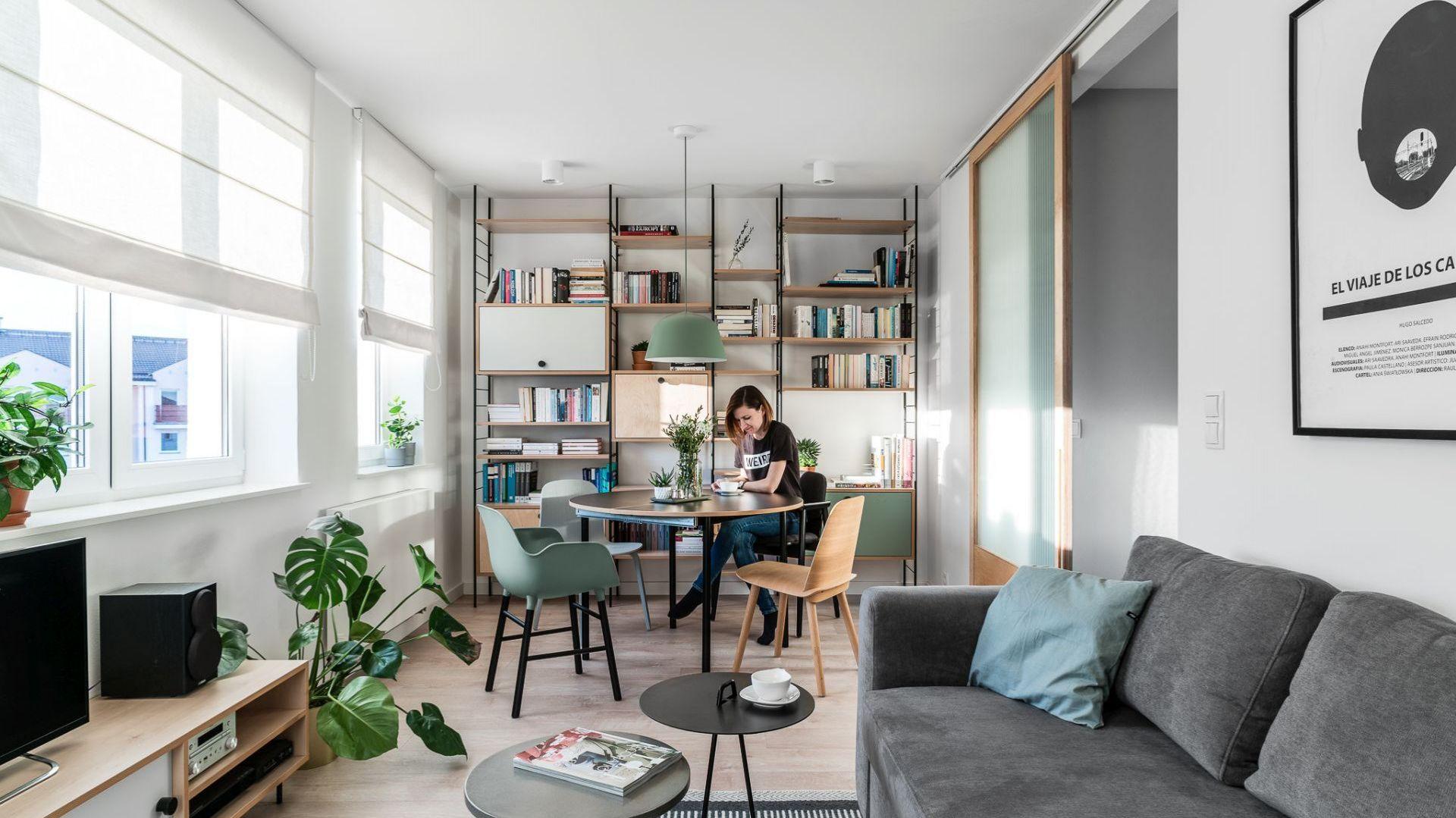 W tym niewielkim salonie szarość kanapy połączono z miętowymi akcentami i naturalnym drewnem. To świetne zestawienie do małych wnętrz. Projekt: Raca Architekci. Fot. Fotomohito