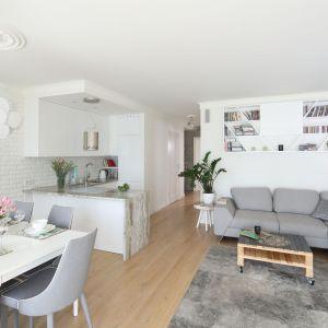 W tym salonie szarość kanapy połączono z bielą ścian. Uwagę zwraca też piękna biała cegła. Projekt Laura Sulzik. Fot. Bartosz Jarosz