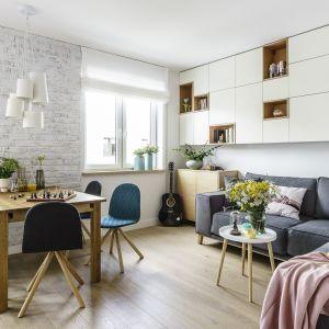Ściana z białoszarej cegły i grafitowa kanapa dobrze wyglądają z naturalnym drewnem i ciekawymi tapicerowanymi krzesłami w modnych niebieskich odcieniach. Projekt Saje Architekci. Fot. Fotomohito