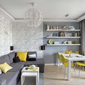 Szarości w tym salonie dodają energii odcienie żółtego oraz ciekawa botaniczna tapeta na ścianie. Projekt Ewa Para. Fot. Bernard Białorucki