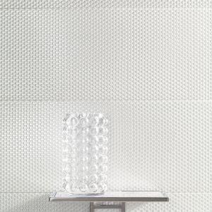 """Płytka dekoracyjna Coma white przypomina ławicę czy sznury pereł – jej połyskująca biel pięknie odbija światło, a na jej strukturę składają się setki drobnych """"perełek"""" właśnie. Dostępna jest w rozmiarze 898x328 mm i cenie 99,88 zł za sztukę."""