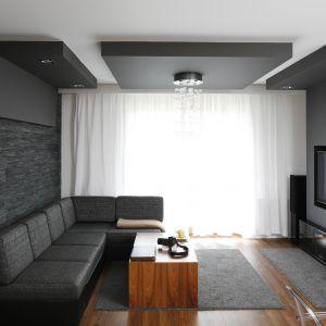 Szaremu wnętrzu przytulności dodaje drewniana podłoga, jasne zasłony oraz drewniana podłoga. Projekt: Michał Mikołajczak. Fot. Bartosz Jarosz