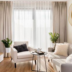 W salonie dominują jasne kolory, ożywione połyskującymi detalami. Tłem dla gustownych dodatków w odcieniach złota są biel, subtelne beże i szarości oraz modny pudrowy róż. Projekt: Joanna Nawrocka. Fot. Łukasz Bera, Lukaszbera.pl