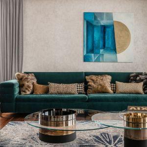 Sofa w kolorze butelkowej zieleń pięknie prezentuje się w zestawie z piaskową tapetą. Projekt: Joanna Safranow. Fot. Fotomohito