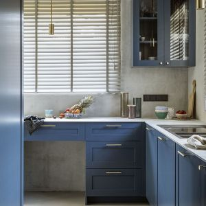 Modne błękitne fronty kuchenne dodają charakteru tej kuchni. Pod oknem w parze z praktycznym zlewozmywakiem stanęła duża bateria z elastyczną wylewką. Projekt Malwina Morelewska. Foto Yassen Hristov