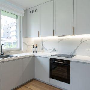 Minimalistyczna kuchnia w tym nowoczesnym mieszkaniu ma zlewozmywak z modną czarną baterią zaprojektowany pod oknem. Fot. Moovin Group