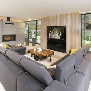Centralnym punktem salonu jest kominek obudowany w nowoczesną bryłę. Frontem do niego usytuowana jest duża, wygodna sofa modułowa. Projekt Dariusz Grabowski