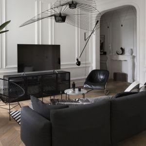 Ściana wykończona białą sztukaterią perfekcyjnie współgra z czarnymi elementami zastosowanymi w salonie. Projekt: Goszczdesign. Fot. Piotr Mastalerz
