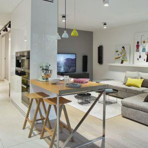 W mieszkaniu na Bielanach łatwy w czyszczeniu, wygodny narożnik w odcieniach szarości doskonale harmonizuje z kolorem ścian i jasnym dywanem marki Louis De Poortere. Projekt: Bibianna Stein-Ostaszewska (Bibi Space). Zdjęcia: Olo Studio