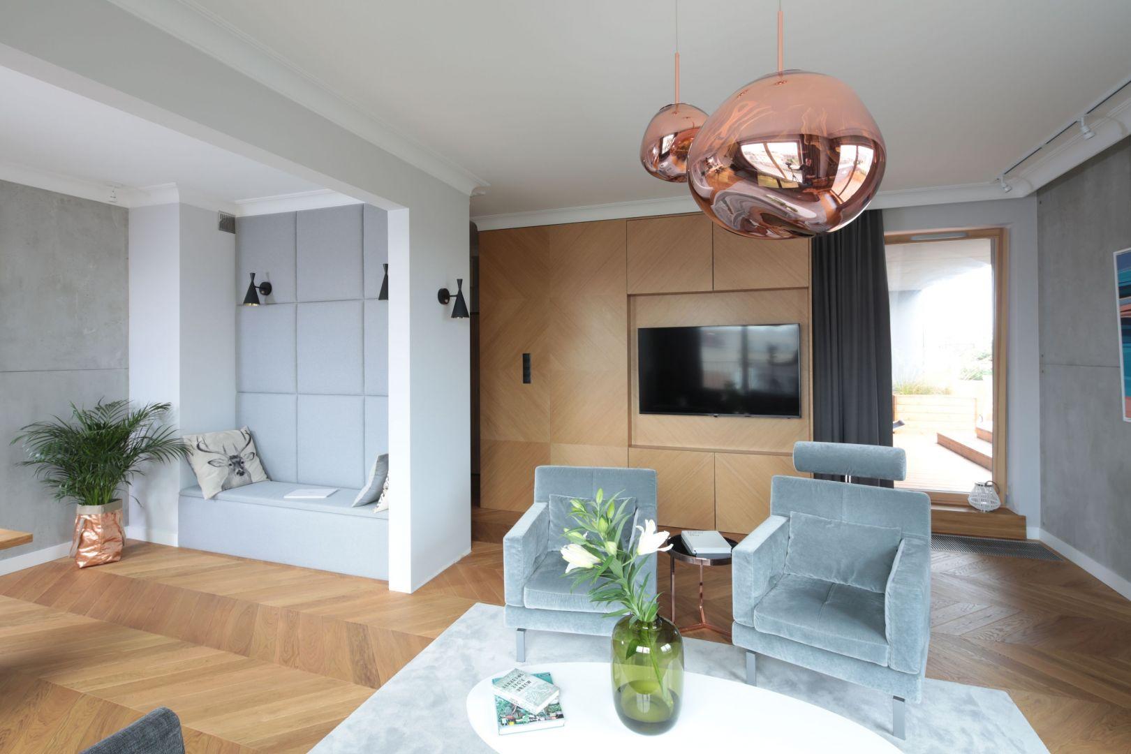 Ścianę za telewizorem wykończono jasnym drewnem, które stanowi również fronty pojemnych szafek. Projekt: Katarzyna Mikulska-Sękalska. Fot. Bartosz Jarosz