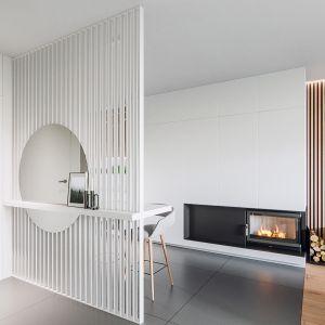 Ciepły charakter salonu budują jasnobrązowa podłoga z drewna oraz ściana telewizyjna. Projekt NABOO STUDIO