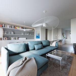 Centralnym punktem przestrzeni wypoczynkowej pozostaje duży narożnik w subtelnym błękicie idealnie oświetlony przez oryginalną lampę wiszącą w eleganckiej bieli. Projekt NABOO STUDIO