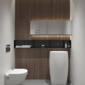 Łazienka zaskakuje nieoczywistą formą, chociaż konsekwentnie projektantki sięgnęły po drewno, biel i różne odcienie szarości. Projekt NABOO STUDIO