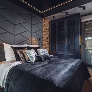 W sypialni dominuje łóżko z tapicerowanym wezgłowiem przechodzącym w sufit podwieszany z elementem czarnego barrisolu w połysku. Projekt: Agnieszka Hajdas-Obajtek. Fot. Wojciech Kic