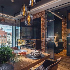 Dzięki wyburzeniu części ściany i wstawieniu szkła, ze strefy dziennej mamy widok na sypialnię, co optycznie powiększa też przestrzeń. Projekt: Agnieszka Hajdas-Obajtek. Fot. Wojciech Kic