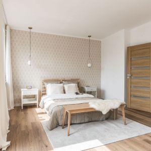 Ścianę za łóżkiem w sypialni zdobi jasna tapeta z delikatnym wzorem. Projekt: Ewelina Matyjasik-Lewandowska. Fot. Tomasz Kazaniecki
