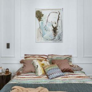 Ścianę za łóżkiem zdobi biała sztukateria na tle której pięknie prezentuję się duży obraz. Projekt: Monika Goszcz-Kłos. Fot. Yassen Hristov