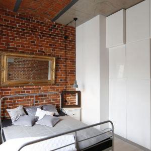 Ścianę za łóżkiem zdobi cegła, która nadaje sypialni nowoczesny klimat. Projekt: Nowa Papiernia. Fot. Bartosz Jarosz