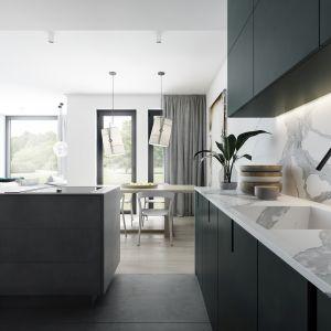 Kuchnia połączona została z jadalnią, a granicę pomiędzy nimi wyznacza jedynie wyspa kuchenna, zróżnicowana podłoga oraz podwieszony sufit z dyskretnie ukrytym w nim oświetleniem w formie spotlightów. Projekt AM.Home