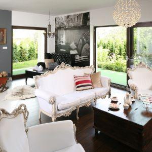 Salon, dzięki dużym przeszkleniom, pięknie otwiera się na ogród. Projekt: Magdalena Konochowicz. Fot. Bartosz Jarosz