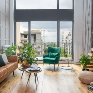Dużym atutem salonu są wielkoformatowe okna. Wpuszczają one do wnętrza światło słoneczne, które idealnie wpisuje się w naturalny styl aranżacji. Projekt: Decoroom. Fot. Marta Behling, Pion Poziom