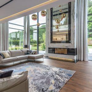 Ogromne okna w salonie wyglądają świetnie. Zdobią je pięknie zdobią jasne, połyskujące zasłony. Projekt: Agnieszka Hajdas-Obajtek. Fot. Wojciech Kic