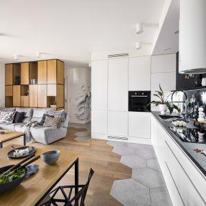 Salon w jasnych kolorach połączony jest z idealnie białą otwartą kuchnię. Drewniana podłoga i meble sprawiają, że wnętrze wygląda naturalnie i bezpretensjonalnie. Projekt Zuzanna Kuc, ZU projektuje. Zdjęcia Łukasz Zandecki