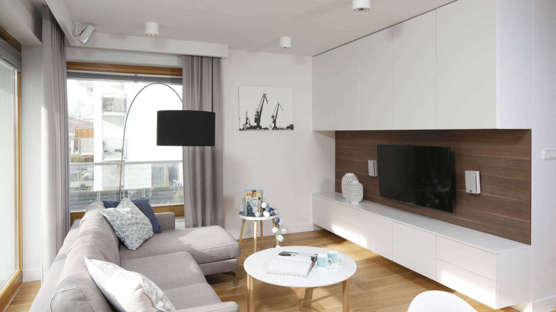 Całą ścianę wokół telewizora zajmu zabudowa wykonana na zamówienie. Szafki na górze i na dole zapewniają sporą powierzchnię na przechowywanie. Projekt: Przemek Kuśmierek. Fot. Bartosz Jarosz