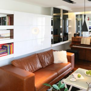 Na kanapą znajduje się praktyczna strefa przechowywania: część półek jest otwarta, część zamknięta. Wykończenie (lakierowany MDF) doskonale prezentuje się w salonie. Projekt: Małgorzata Mazur. Fot. Bartosz Jarosz