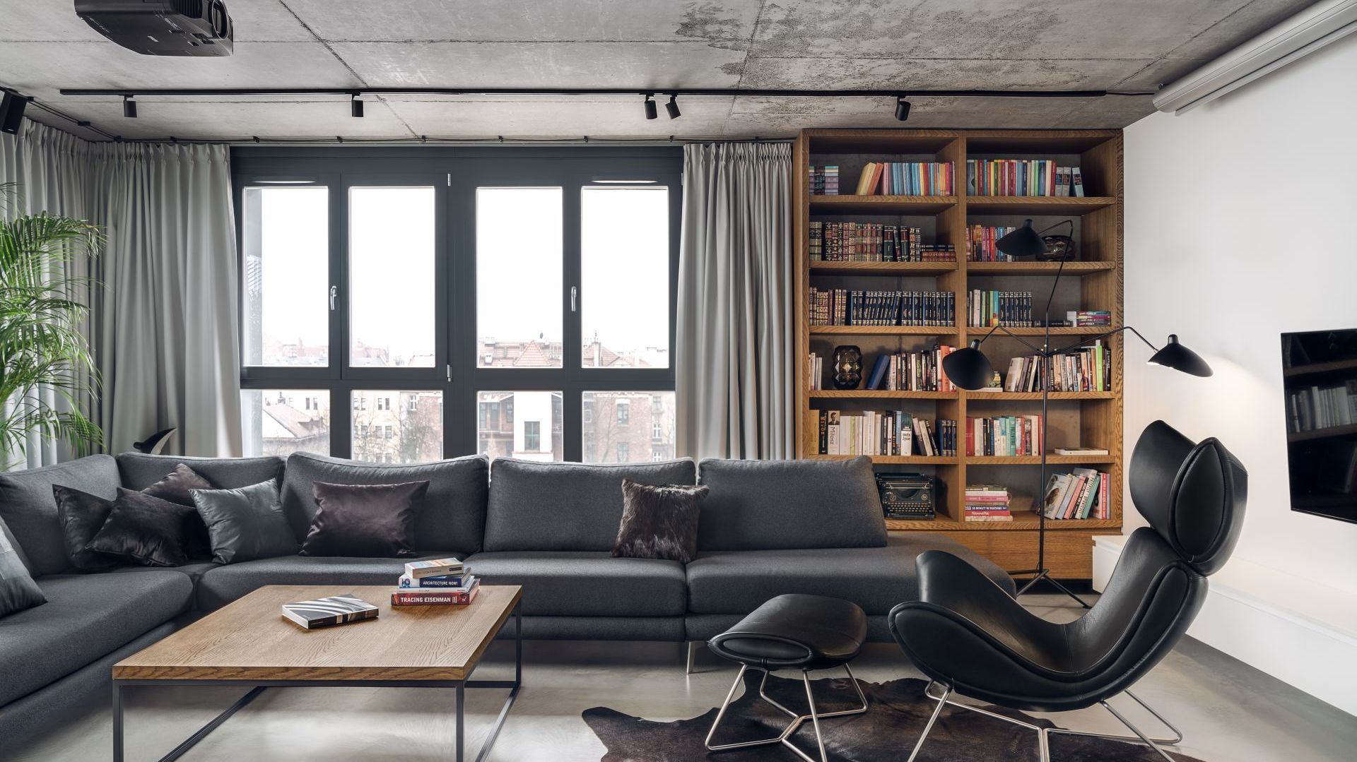 Drewniana otwarta szafa na ścianie za kanapą zapewnia spora ilość miejsc na domową biblioteczkę. Projekt: BLACKHAUS Karol Ciepliński Architekt. Fot. Tom Kurek
