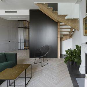 Drewniane kilkubiegowe schody osłonięte od strony salonu dekoracyjną czarną ścianą. Projekt: Madama. Fot. Yassen Hristov