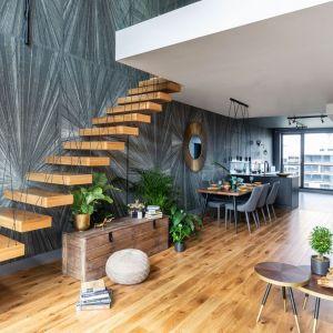 """Drewniane schody wizualnie """"wiszą w powietrzu dzięki podwieszanej konstrukcji i wtopieniu stopni w ścianę. Projekt Decoroom. Fot. Marta Behling, Pion Poziom.jpg"""