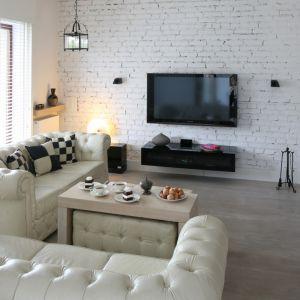 Ścianę za telewizorem zdobi biała cegła, które doskonale wygląda w zestawieniu z miękkimi, pikowanymi e kanapami w stylu chesterfield. Projekt: Monika Włodarczyk, Jarosław Jończyk. Fot. Bartosz Jarosz