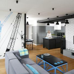 Ściana za telewizorem wykończona jest białą cegłą. Ścianę przy kanapie zdobi z kolei tapeta. Projekt: Monika i Adam Bronikowscy. Fot. Bartosz Jarosz