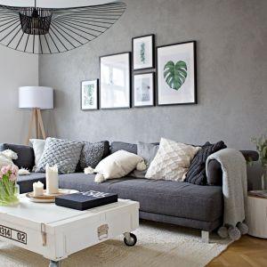 Jasne dekoracje rozjaśniają i ocieplają dużą ciemnoszara sofę. Projekt SHOKO design